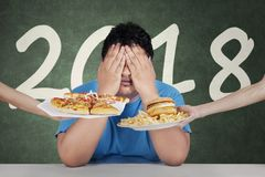 Fat man with number 2018. Image of fat man refusing to eat unhealthy food while sitting with number 2018 background Stock Photography