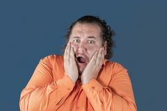 Fat man in orange shirt holds his hands over his face on blue background. He is very scared stock photography
