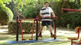 Fat man on outdoor air walker stock video