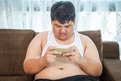 Fat  man play game with his smartphone Royalty Free Stock Photos