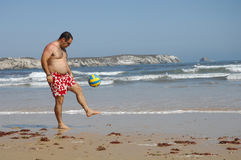Fat man playing with a ball on the beach Royalty Free Stock Image