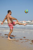 Fat man playing with a ball on the beach Royalty Free Stock Photos