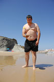 Fat man playing beach tennis on the beach Stock Image
