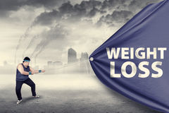 Fat man pulling a weight loss banner. Shot outdoors Stock Image