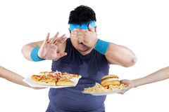 Fat man rejecting junk food. Fat man rejecting to eat junk food. Isolated on white background Royalty Free Stock Photo