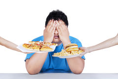 Fat man rejecting junk food 2. Fat man rejecting to eat junk food. Isolated on white background Stock Photo