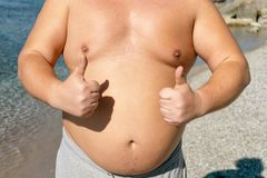Fat man is resting and enjoying the sun on the sunny beach stock images