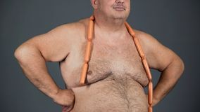 Fat man with sausages round his neck, poor quality nutrition, obesity problem. Stock footage royalty free stock photography