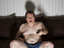 Fat man shocked while watching TV. Man who needs to cut some weight doesn't get off the couch watching TV Stock Photography
