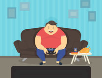 Fat man sitting at home on the sofa playing video games and eating Stock Photography