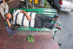 Fat man sleeping on a bench. He is not a homeless, he is just having a rest. Chinatown, Bangkok, Thailand Stock Photos