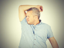 Fat man, smelling sniffing his armpit, something stinks bad, fou Royalty Free Stock Image