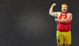 Fat man in sports clothes measures his arm with a centim royalty free stock image