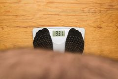 The fat man stood on the scales royalty free stock image
