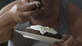 Fat man swallowing up chocolate cake, unhealthy food, diet get out of control. Stock footage stock video