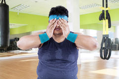 Fat man tired after workout. And covering his face Stock Photography