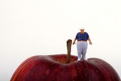 Fat man on the top of a red apple Royalty Free Stock Photo