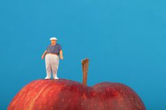Fat man on the top of a red apple Royalty Free Stock Image