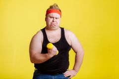 Fat man try to lift small yellow dambbell. Fat funny man try to lift small yellow dambbell royalty free stock photo