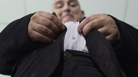 Fat man trying to fasten a button on his jacket, extra weight, bottom view