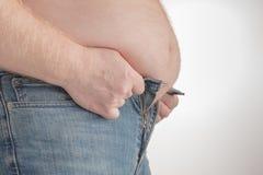 Fat man trying to put on pants. Big Paunch Stock Photos