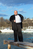 Fat man in tuxedo on pier Stock Photo