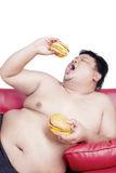Fat man and two big hamburger. Image of fat man eating two big hamburgers on the red couch, isolated on the white background Royalty Free Stock Photos