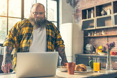 Fat man using notebook in kitchen Stock Images