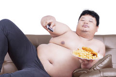 Fat man watch tv on sofa. Portrait of lazy fat man sitting on the sofa while watching tv and holding junk food Stock Photography