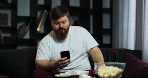 Fat man watches TV and types something in his smartphone. He orders home food. The concept of malnutrition, food. Delivery, rest stock video