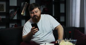 Fat man watches TV and types something in his smartphone. He orders home food. The concept of malnutrition, food. Delivery, rest stock video footage