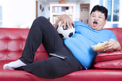 Fat man watching football match at home. Overweight man sitting lazy on sofa while drinking beer and eat snack Stock Image