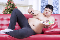 Fat man watching tv in christmas day Royalty Free Stock Image