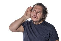 Fat man wearing a casual outfit, trying to hear someone putting his hand on his ear, standing on a white background royalty free stock image