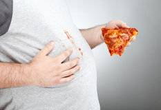 Fat man wiping pizza sauce on his shirt. An overweight man holds a slice of pizza with a missing bite. He has pizza sauce on his hands and is wiping it on his Royalty Free Stock Image