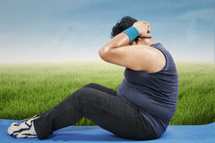 Fat man workout on mattress outdoors Stock Images