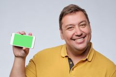 Fat man in a yellow shirt pleased with himself holding a phone with green screen. He is happy with success or achievement in the phone game or sales Stock Image
