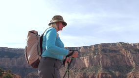 Fat mature woman with trekking poles and a backpack hiking in the grand canyon. Fat mature caucasian woman overweight, hiking with trekking poles and backpack on stock video