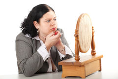 Fat, overweight woman applying lipstick Stock Image