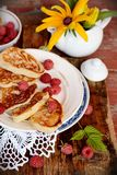 Fat pancakes with fresh raspberries. Pancakes decorated with berries on wooden table Royalty Free Stock Images