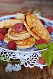 Fat pancakes with fresh raspberries. Pancakes decorated with berries on wooden table Stock Photography