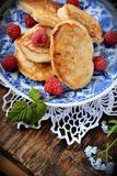 Fat pancakes with fresh raspberries. Pancakes decorated with berries on wooden table Stock Images