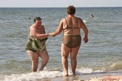 Fat people in the sea. Urzuf, Ukraine - July 24, 2014: the fat woman helps her friend out of the water The picture was taken on the shore of the Sea of Azov stock photo