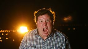 Fat raged man standing and screaming in panic or terror at night outdoor, portrait. Cry of the devil stock footage