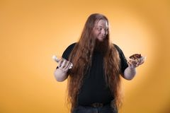 A fat red-haired man holds water and a cake. stock photos