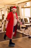 Fat Santa posing on left leg in the gym. Embarrassed Santa Claus is standing on left leg on small scales in the gym. Fat man is discouraged that he gained Royalty Free Stock Photo