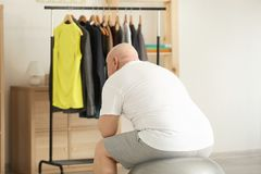 Fat senior man looking at rack with tight clothes at home. Weight loss concept Royalty Free Stock Photography
