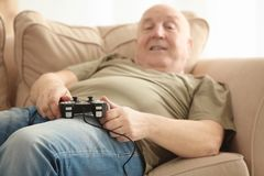 Fat senior man playing videogame while lying on sofa at home, closeup. Sedentary lifestyle concept Royalty Free Stock Image