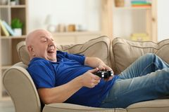 Fat senior man playing videogame while lying on sofa at home. Sedentary lifestyle concept Stock Photo