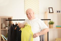 Fat senior man with small-sized clothes at home. Weight loss concept Stock Photo